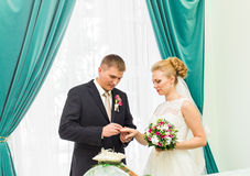 Groom slipping ring on finger of bride at wedding Royalty Free Stock Photos