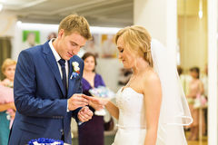Groom slipping ring on finger of bride at wedding Stock Photos