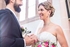 Groom slipping ring on finger of bride at wedding Stock Photo
