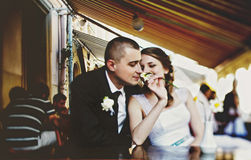 Groom smells a flower in the bride's hand while they rest in a s Royalty Free Stock Photo