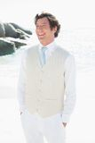 Groom smiling with hands in pockets. At the beach Royalty Free Stock Image