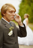 Groom speaks by phone , forgotten about bride Royalty Free Stock Photo