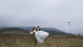 Groom Spining Around with his Wife in Hands. Autumn mountain. Groom Spining Around with his Wife in Hands stock video
