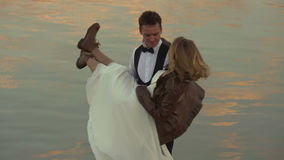 Groom is spinning his bride near water stock footage