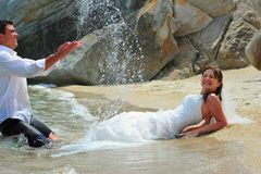 Groom splashing bride with sea water drops Royalty Free Stock Photo