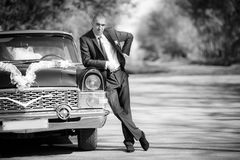 Groom  stand near a black retro of the car Stock Image