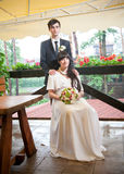 Groom standing behind sitting bride Royalty Free Stock Photos