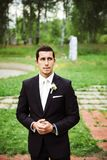Groom standing in a green area royalty free stock photos