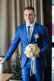 Groom standing and holding wedding bouquet Royalty Free Stock Photos