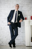 Groom standing near fireplace Royalty Free Stock Image