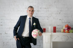 Groom standing near fireplace Stock Photo