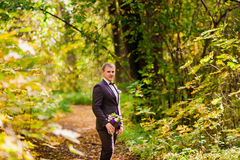 The groom stands in the autumn forest on a background of yellow leaves Royalty Free Stock Image