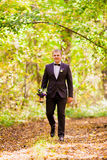 The groom stands in the autumn forest on a background of yellow leaves Stock Photo