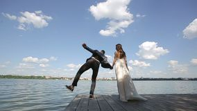 Groom stands near bride and jumping. Lovely wedding couple stands near lake. Slow motion stock footage