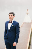 Groom stands near  lake   bride standing on pier Royalty Free Stock Photo