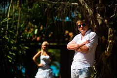 Groom stands near the tropical tree, and behind him is the bride stock photo