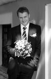 Groom stood with bouquet. A portrait of a handsome groom seen here stood with a bouquet of flowers smiling Stock Photo