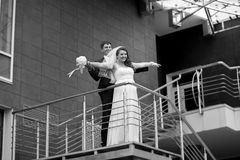 Groom stretching out brides hands on stairs Royalty Free Stock Images