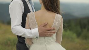 The groom strokes the bride`s back near mountain hills. Wedding couple stock video footage