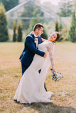 Groom in stylish blue suit holding beautiful bride with white wedding dress outdoor on lawn. Greenhouse at background Stock Photo