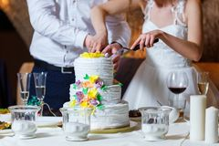 Groom in suit and bride in white dress cut beautiful multi level. Wedding cake, decorated with cream yellow flowers, greenery and gold. Delicious dessert at Royalty Free Stock Images