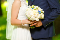 The groom in a suit and the bride in  white dress standing side by   are holding bouquets of  flowers Stock Photos