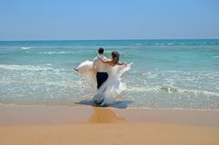 The groom in a suit carries on his hands the bride in a wedding dress in the waters of the Indian Ocean. Wedding and honeymoon royalty free stock images