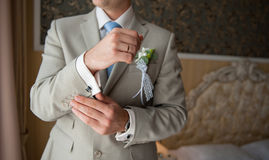 Groom in a suit, hands wear cufflinks Royalty Free Stock Image