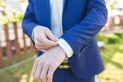 Groom in a suit. Hands wear cufflinks Royalty Free Stock Photo