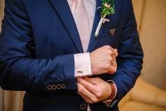 Groom in a suit hands wear cufflinks in room.  Stock Photo
