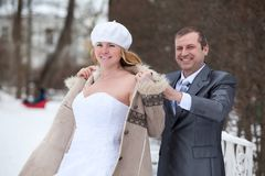 Groom in suit helps to slip bride`s fur coat on women shoulder, woman in white wedding dress in winter park Stock Photos