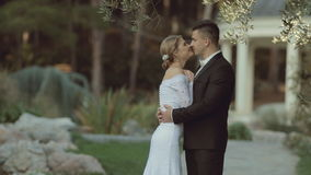 The groom in a suit hugging the bride in an stock video footage