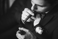 The groom in a suit smoking cigar Stock Images