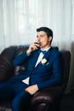The groom in a suit smoking cigar Royalty Free Stock Photos