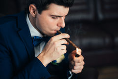 The groom in a suit smoking cigar Stock Photos