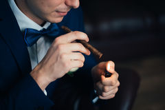 The groom in a suit smoking cigar Stock Photography