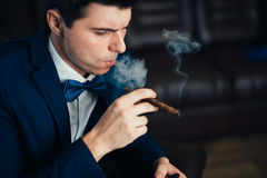 The groom in a suit smoking cigar Stock Image