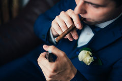 The groom in a suit smoking cigar Royalty Free Stock Image