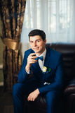 The groom in a suit smoking cigar Royalty Free Stock Photography