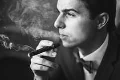 The groom in a suit smoking cigar Royalty Free Stock Images