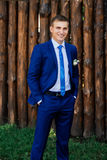 The groom in a suit stands near the wooden wall from logs Royalty Free Stock Photo