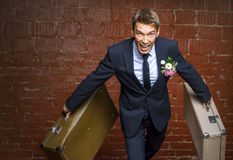 Groom in a suit and two suitcases runs away Royalty Free Stock Photography