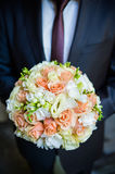 The groom in a suit or Young girl-bride or bridesmaid is holding a wedding bouquet. The groom in a suit or Bridesmaid is holding a wedding bouquet before church Royalty Free Stock Photography