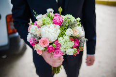 The groom in a suit or Young girl-bride or bridesmaid is holding a wedding bouquet. The groom in a suit or Bridesmaid is holding a wedding bouquet before church Stock Photo