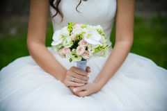 The groom in a suit or Young girl-bride or bridesmaid is holding a wedding bouquet. The groom in a suit or Bridesmaid is holding a wedding bouquet before church Stock Photography