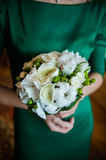 The groom in a suit or Young girl-bride or bridesmaid is holding a wedding bouquet. The groom in a suit or Bridesmaid is holding a wedding bouquet before church Stock Image