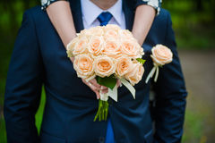 The groom in a suit or Young girl-bride or bridesmaid is holding a wedding bouquet. The groom in a suit or Bridesmaid is holding a wedding bouquet before church Stock Images
