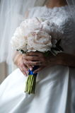 The groom in a suit or Young girl-bride or bridesmaid is holding a wedding bouquet. The groom in a suit or Bridesmaid is holding a wedding bouquet before church Royalty Free Stock Photo