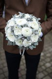The groom in a suit or Young girl-bride or bridesmaid is holding a wedding bouquet Stock Image