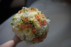 The groom in a suit or Young girl-bride or bridesmaid is holding a wedding bouquet Royalty Free Stock Image